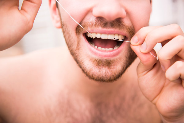 Man flossing to keep his teeth clean