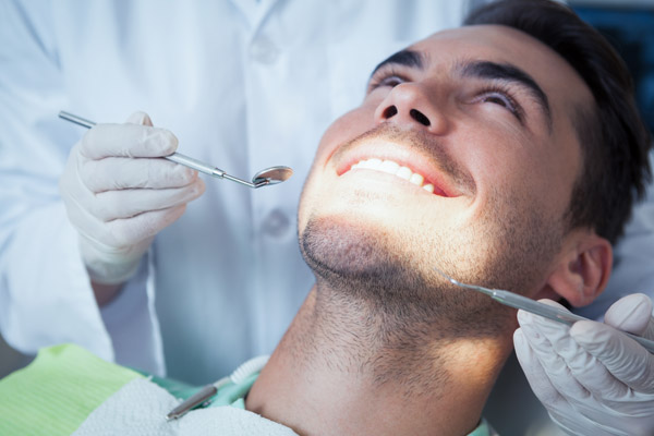 Man in dentist chair getting treatment